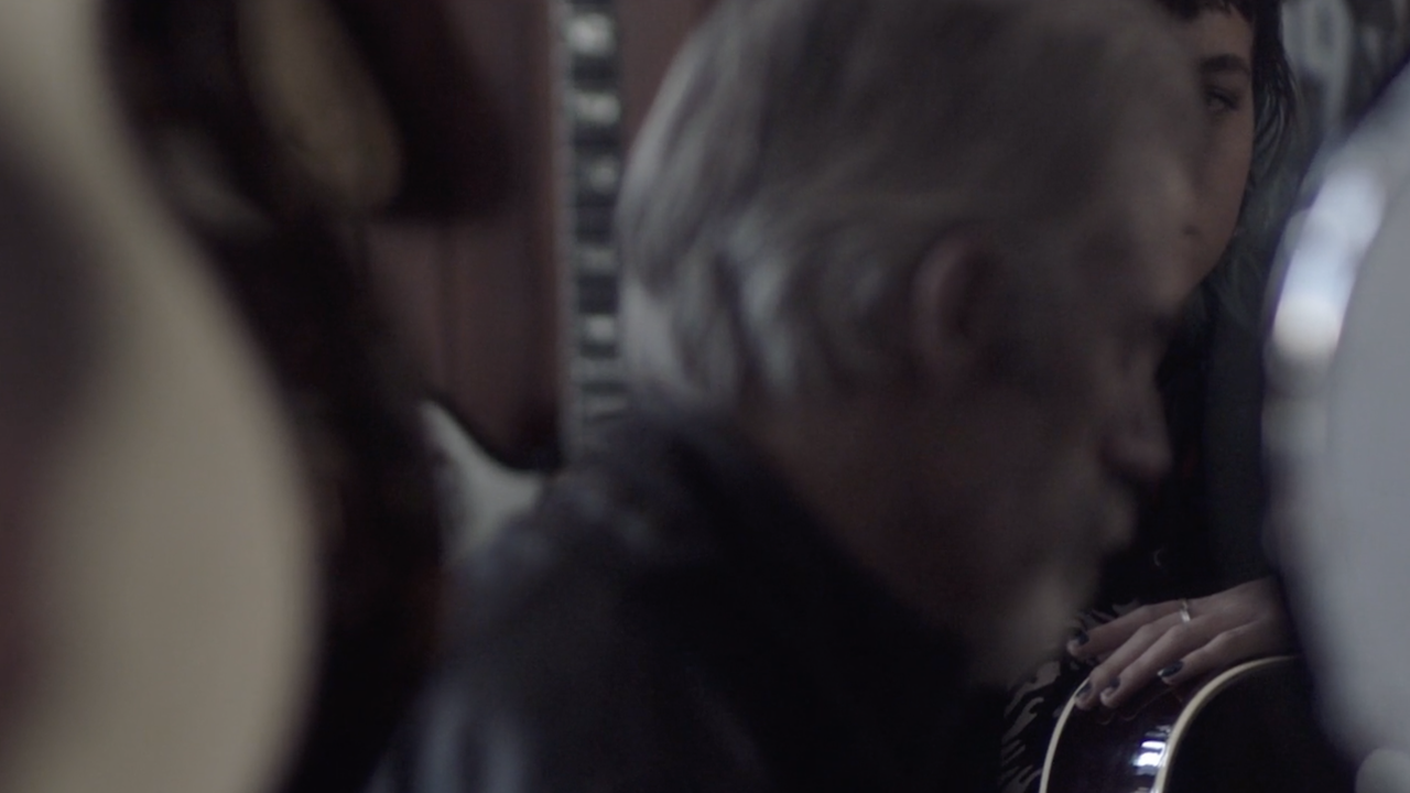 Screenshot from This Perfect Day - Young woman with guitar looking at older man